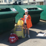 En ung Nykvarns-gymnast framför en återvinningsbehållare.
