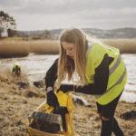 En ung tjej plockar skräp från strand och slänger i en gul Städa Sverige-säck..