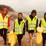 Fyra tjejer går på en strand i Åhus, med gula skräpsäckar i näven. Det är regnväder och tjejerna gör lite grimaser till följd av att de blir blöta.